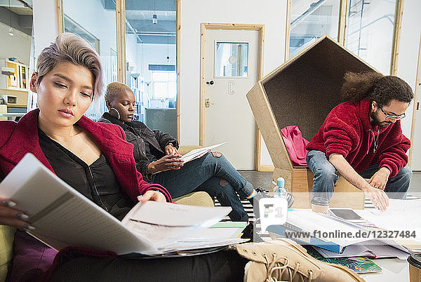 Creative business people reviewing paperwork in office