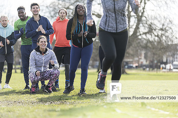 Team cheering woman doing speed ladder drill in sunny park