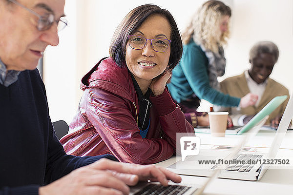 Portrait smiling  confident senior businesswoman using laptop in conference room meeting