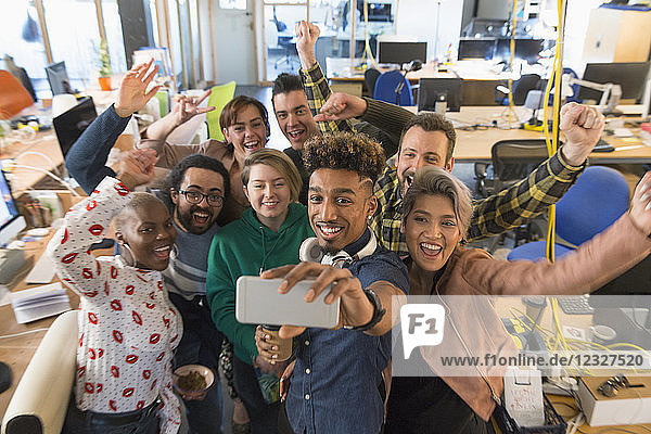 Enthusiastic creative business team cheering  taking selfie in office