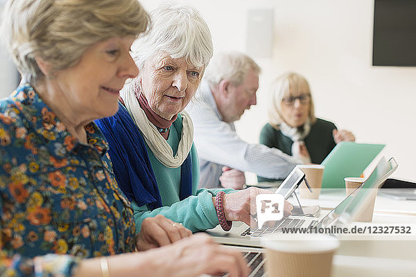 Senior businesswomen using laptops in conference room meeting