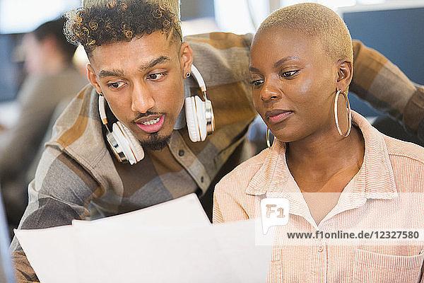 Focused creative business people reviewing paperwork