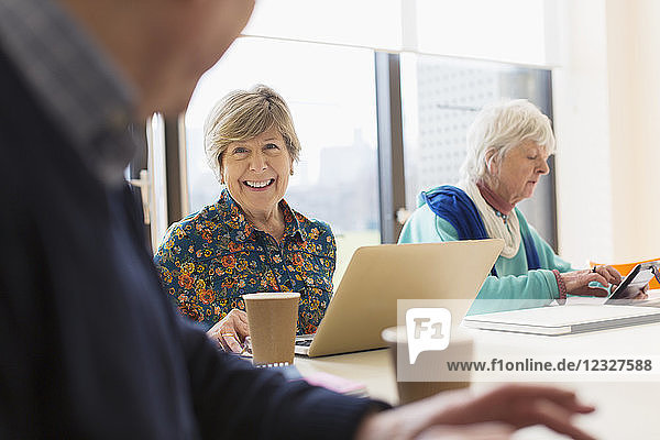 Senior businesswoman using laptop in conference room meeting