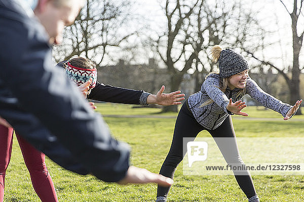 Smiling woman stretching  exercising in park