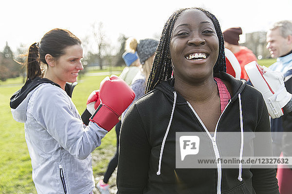 Portrait smiling  confident woman boxing in park with friends