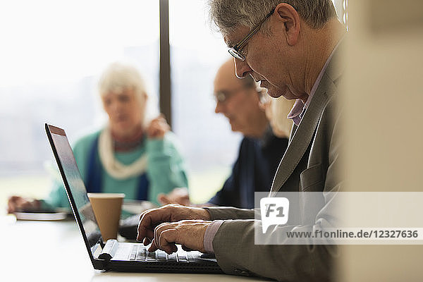 Focused senior businessman using laptop in conference room meeting