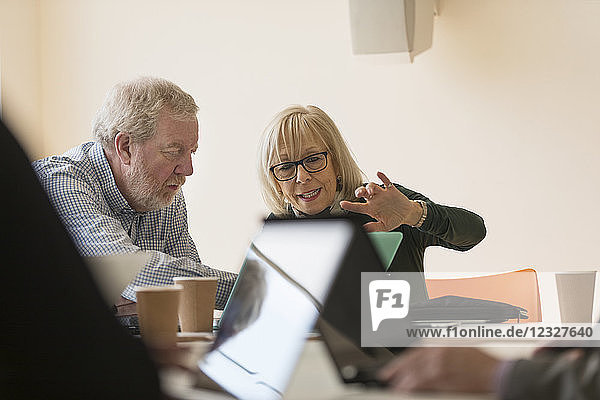 Senior business people using laptop in conference room meeting