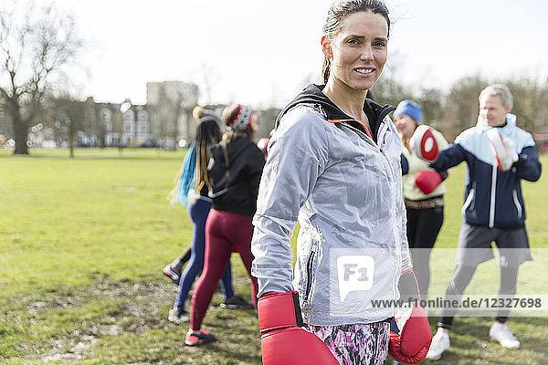 Portrait confident  tough young woman boxing in park