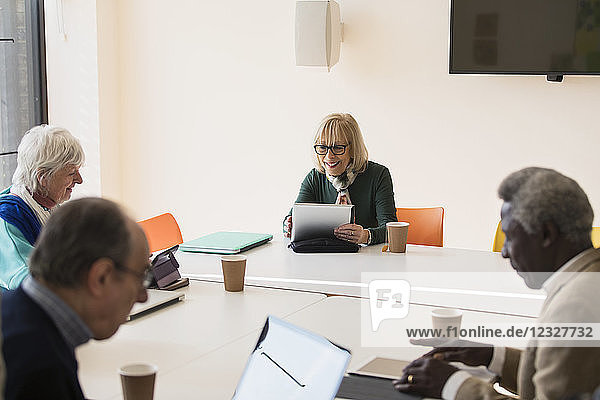 Senior businesswoman using digital tablet  leading conference room meeting
