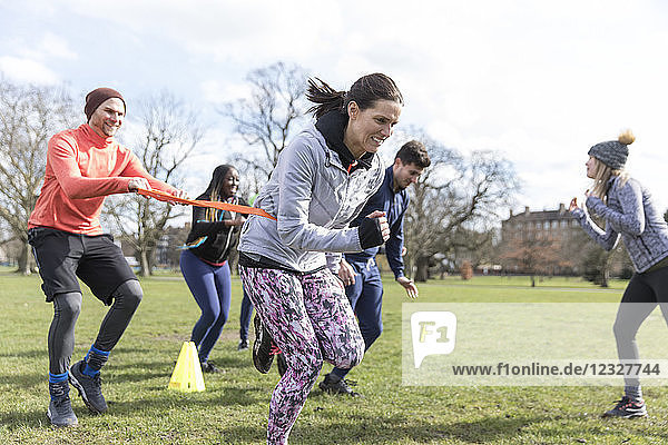 People racing  doing team building exercise in sunny park
