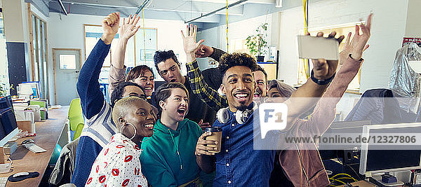 Enthusiastic creative business team taking selfie in office