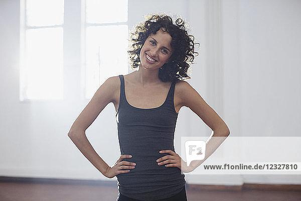 Portrait smiling  confident young female dancer in dance studio