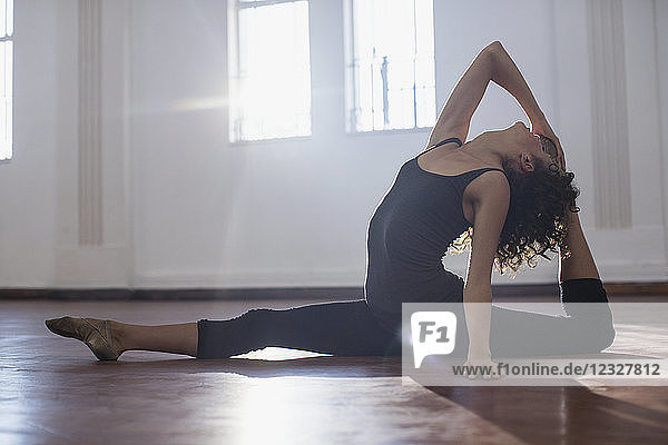 Graceful young female dancer stretching in dance studio