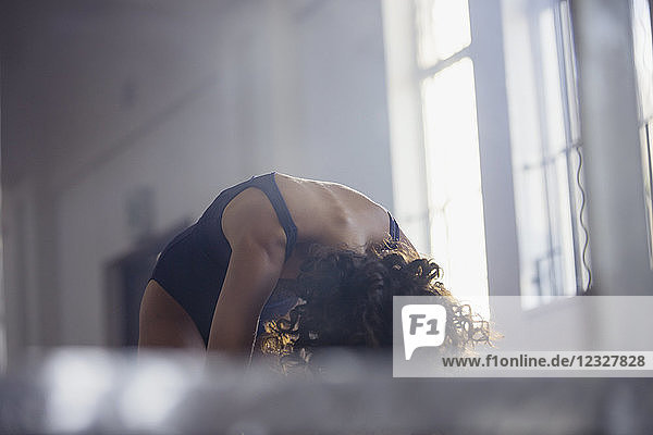 Reflection of young female dancer practicing in dance studio mirror