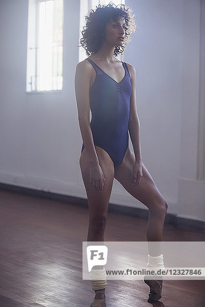 Young female ballet dancer stretching toes in dance studio