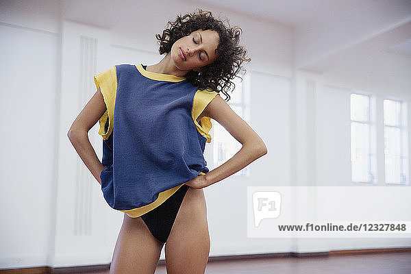 Young female dancer stretching neck in dance studio