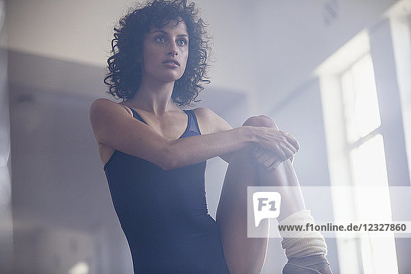 Focused young female dancer stretching leg in dance studio