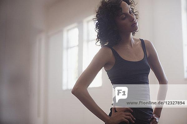 Focused  dedicated young female dancer resting in dance studio
