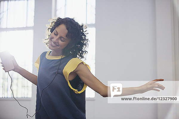 Carefree young female dancer listening to music with headphones and mp3 player