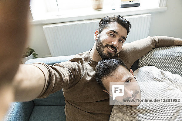 Smiling gay couple taking selfie while relaxing on sofa in living room at home