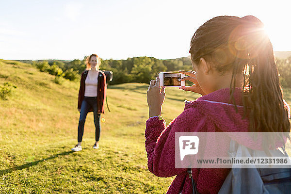 Rear view of girl photographing mother standing on field against clear sky during sunset