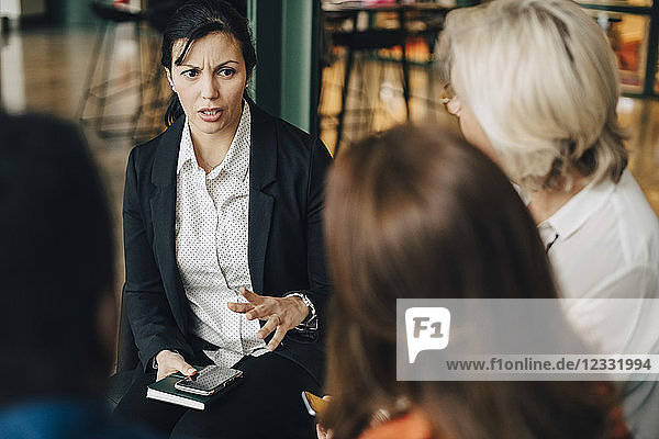 Businesswoman explaining colleagues in meeting at conference