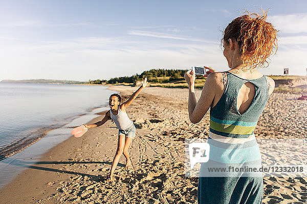 Rear view of woman photographing playful daughter standing on shore at beach against sky