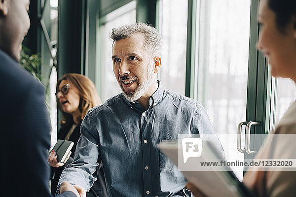 Mature businessman greeting young colleague in meeting at office