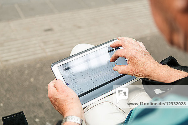 High angle view of senior man using digital tablet while sitting in city