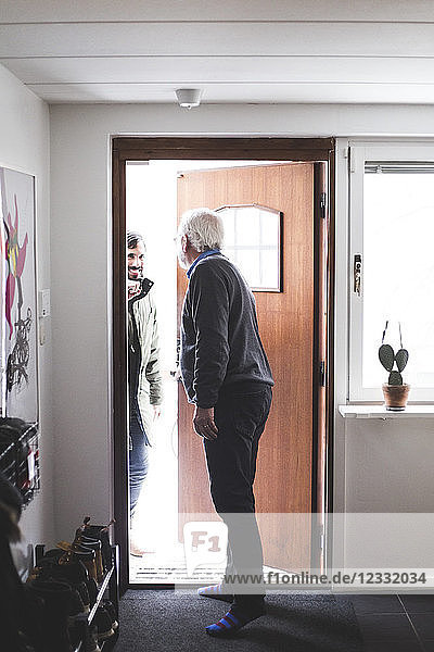 Doctor opening door for patient at home office