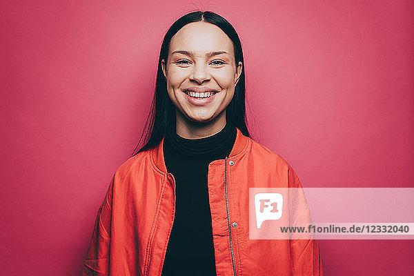Portrait of smiling woman wearing orange jacket over pink background