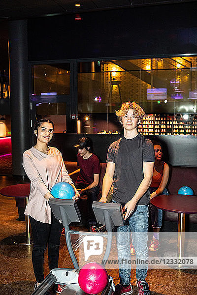 Full length of teenage friends standing by computer at bowling alley
