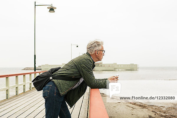 Side view of senior man leaning on railing while looking at sea against clear sky