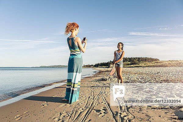 Woman photographing daughter standing on shore at beach against sky