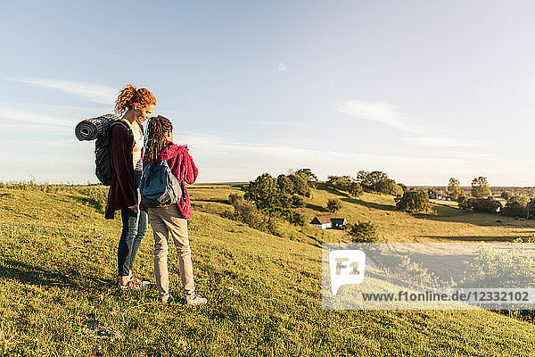 Full length of mother and daughter with backpacks standing on hill against sky during sunset
