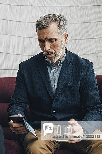 Mature businessman having tea while using smart phone on couch at office