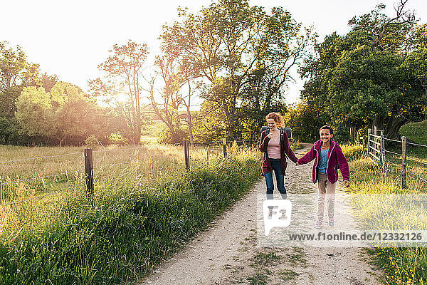 Full length of smiling mother and daughter holding hands walking on dirt road in forest