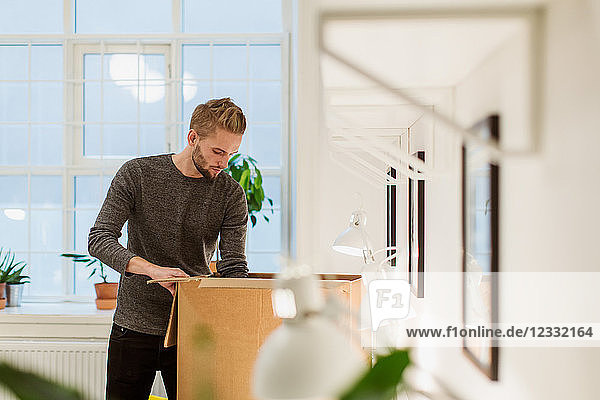 Young businessman opening cardboard box at illuminated creative office