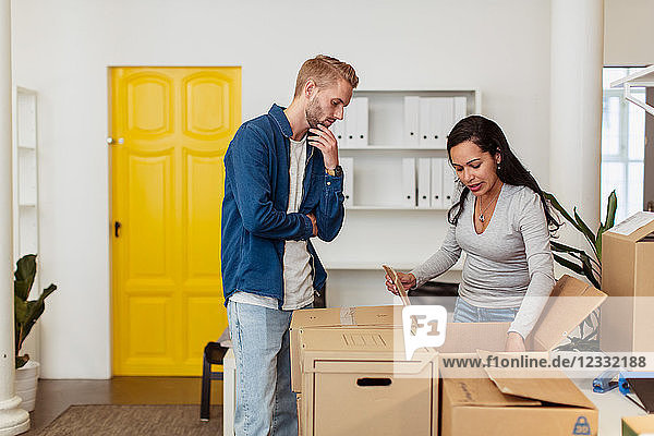 Young businessman looking at businesswoman opening cardboard box at office