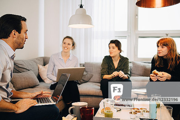 Female professionals looking at businessman sitting with laptop on sofa in creative office