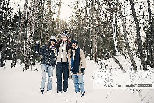Full length of smiling friends standing against trees on snow covered field