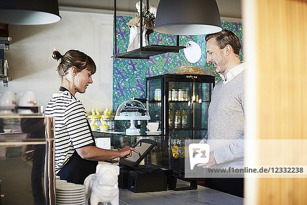 Male customer looking at female barista using cash register in cafe