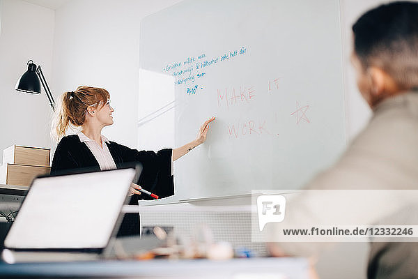 Low angle view of young businesswoman standing by acrylic glass with colleague in board room at office