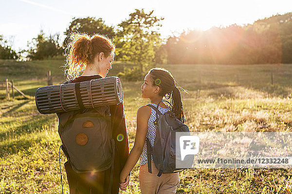 Rear view of woman and girl with backpacks hiking on grass at public park during sunset