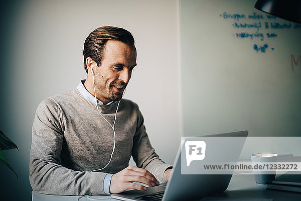 Smiling businessman using laptop while listening to in-ear headphones at creative office