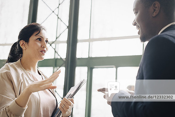 Businesswoman sharing ideas with male coworker in meeting at office