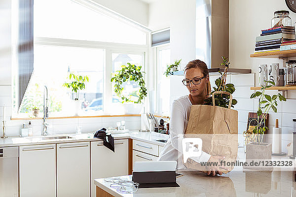 Woman holding paper bag while looking at digital tablet in kitchen