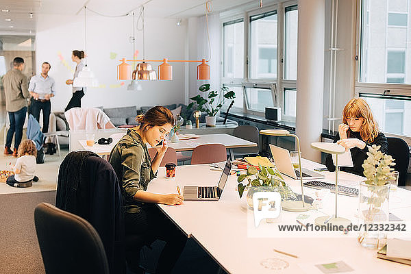Female business colleagues working at illuminated desk in creative office