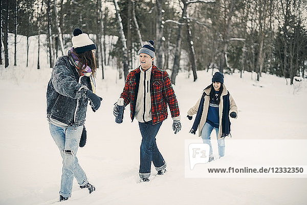Full length of friends talking while walking on snow covered field