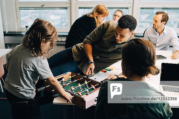 High angle view of boy playing foosball with businessman on desk amidst colleagues at creative office